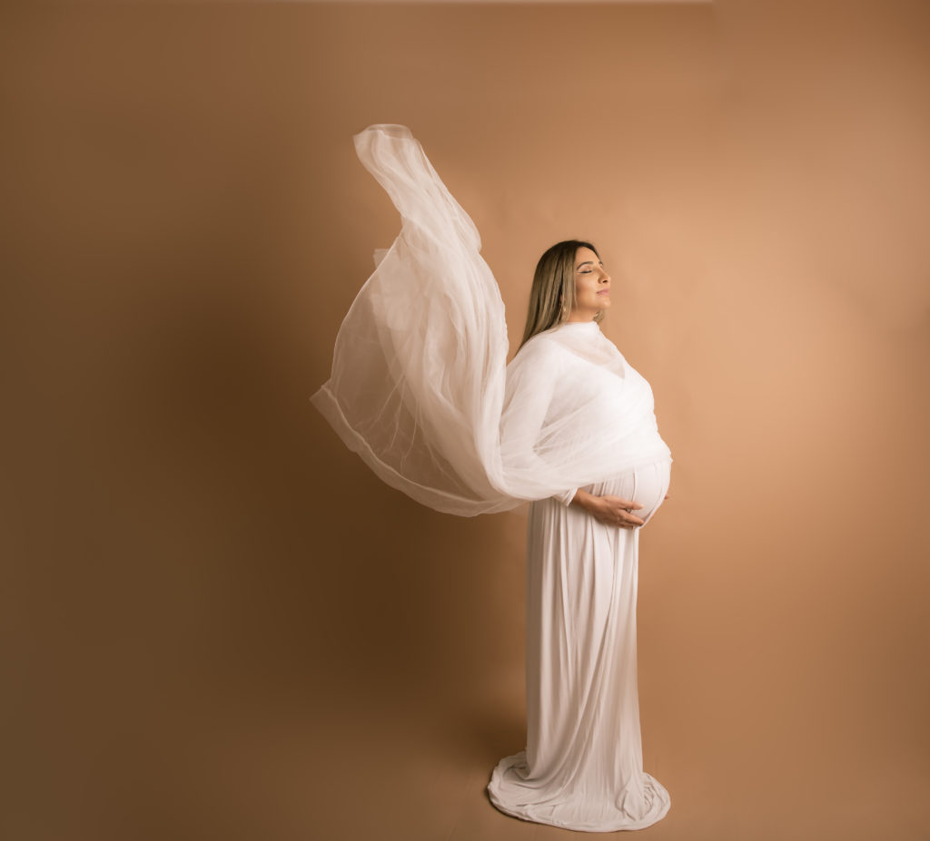 Expectant mother in white dress with flying fabric, Studio maternity photoshoot, Maternity mother to be photo session mother and baby photographer maternity South West London SW19