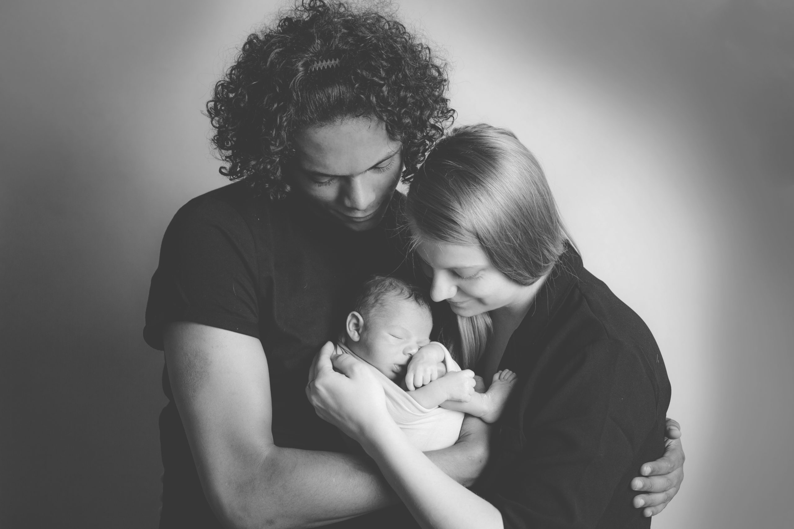 Black and white B&W Family and children photographer in South West London SW19 family portrait photography White mum dark skin dad holding their beautiful baby boy natural colours classic family portrait