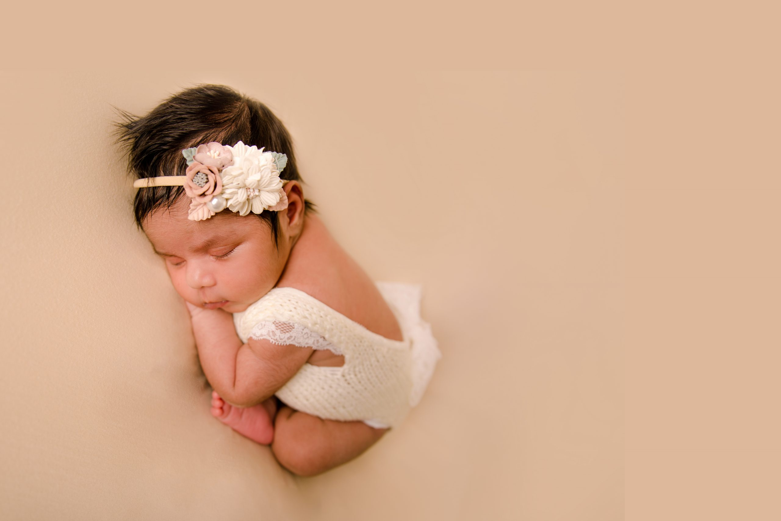 newborn baby girl on beige background dressed in white romper taco pose