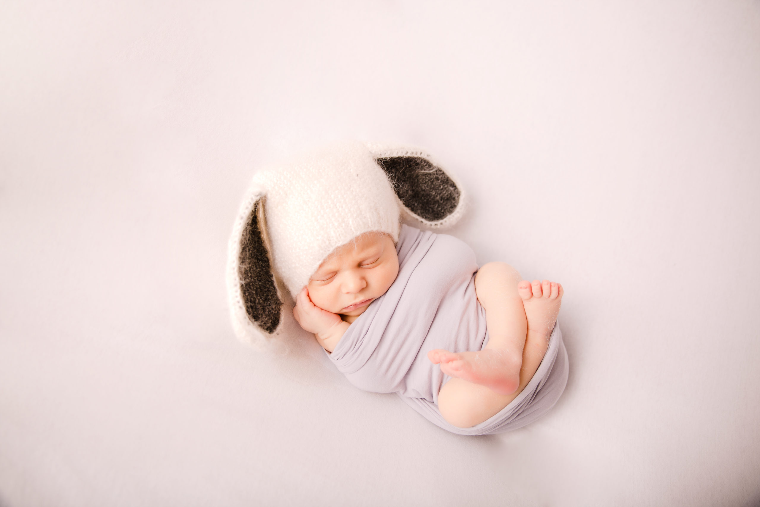 Newborn baby and Family Photographer in South West London Wimbledon Baby Boy in white hat on a white background