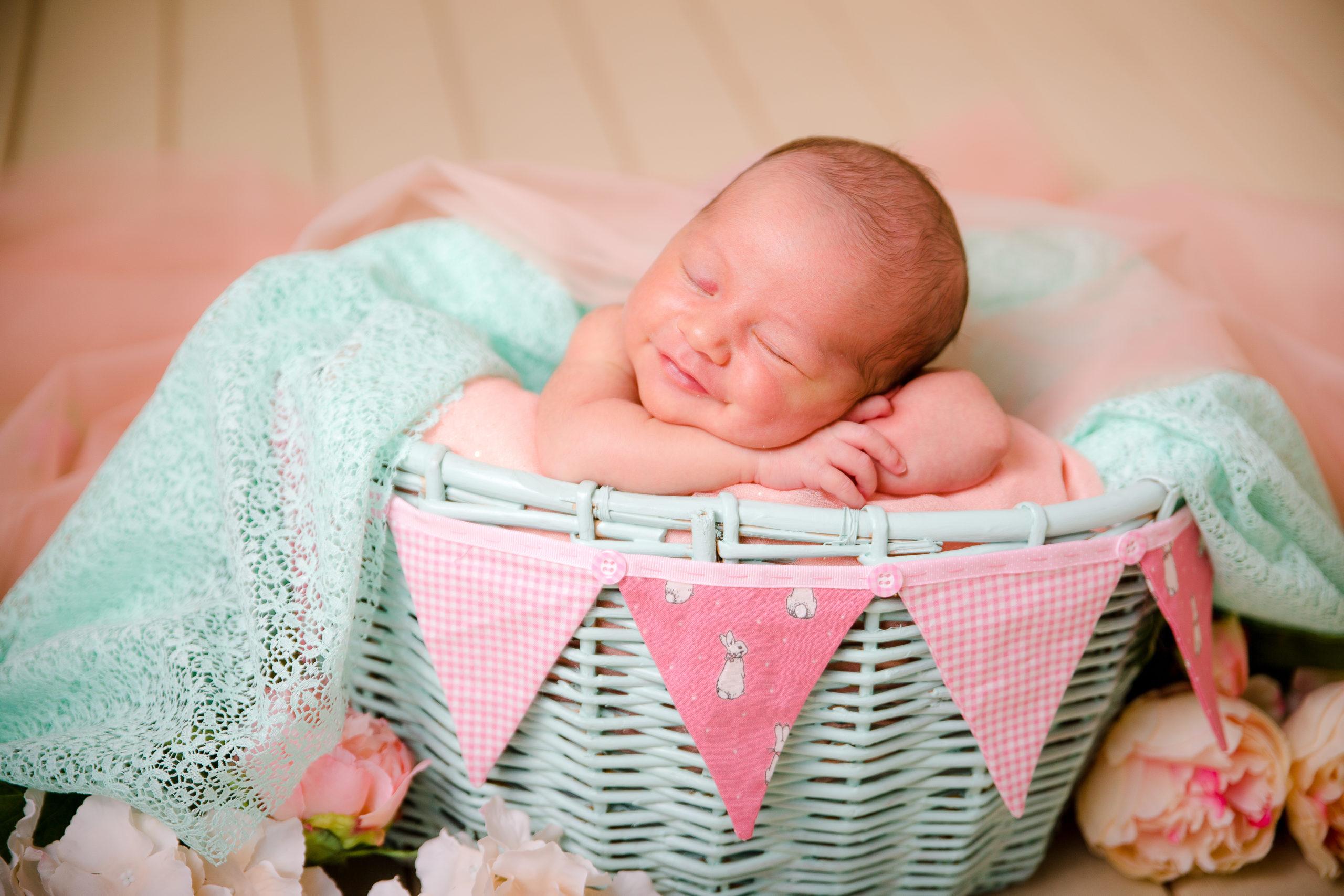 Newborn baby and Family Photographer in South West London Wimbledon Baby girl in cream min and pink colours in a basket Studio newborn photography in South West London Wimbledon SW19