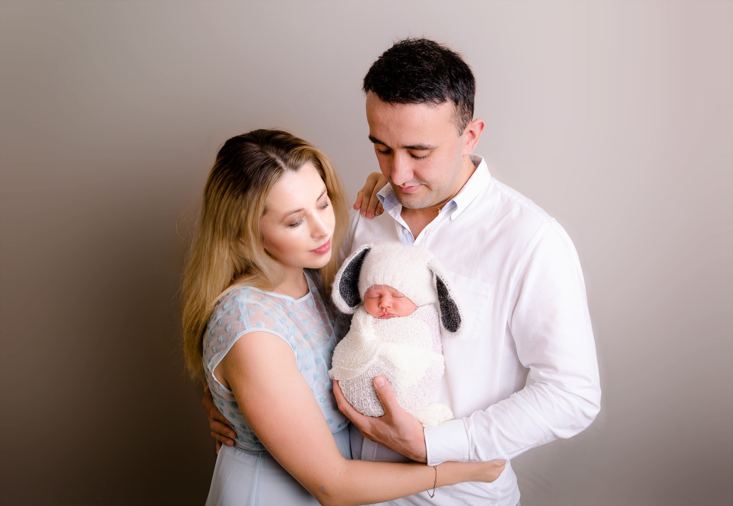 Family children and newborn baby photography new parents are holding their baby girl wrapped family portrait South West London Photo Studio SW19 Wimbledon