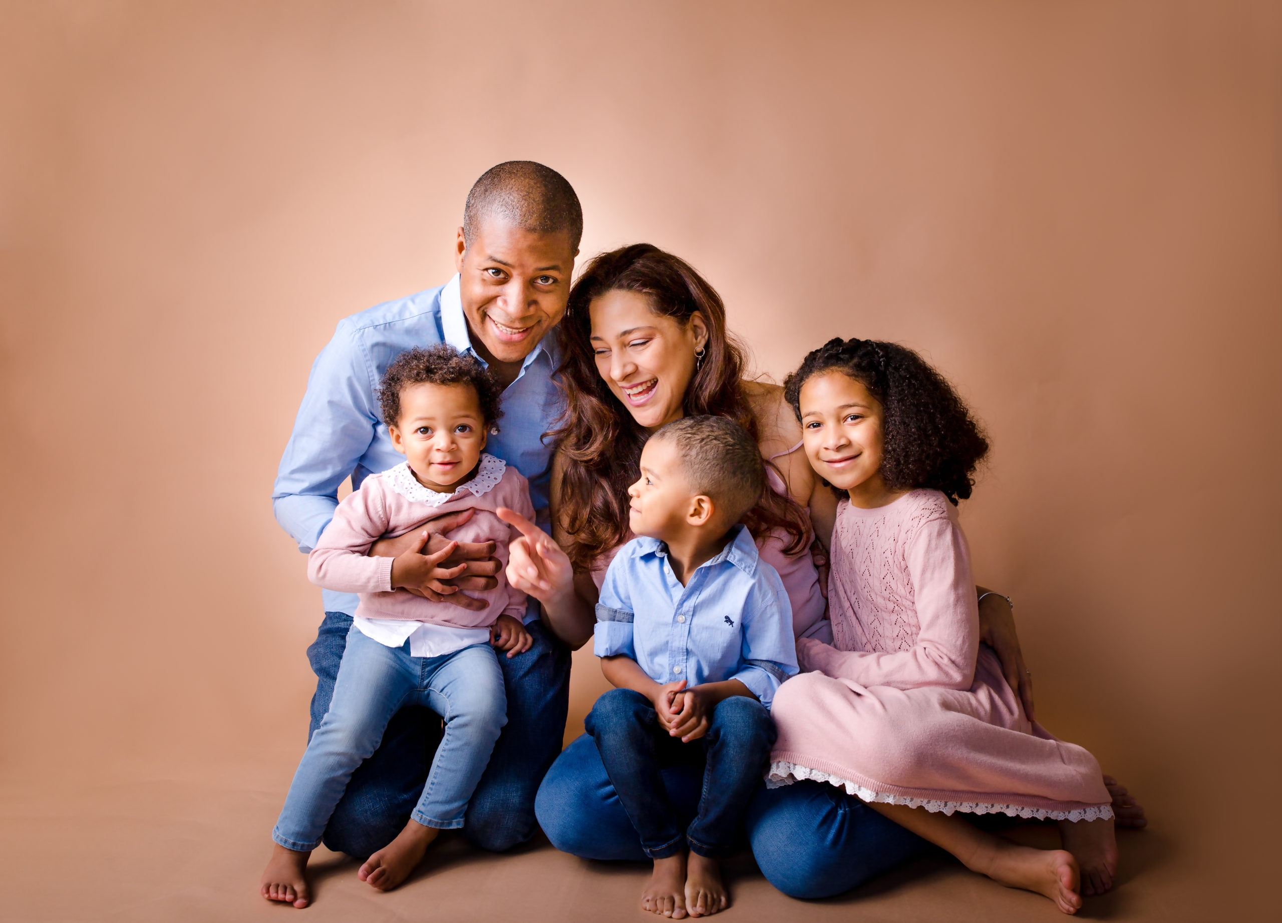 Family and children photographer in South West London SW19 family portrait photography White mum dark skin dad holding their three beautiful children natural colours classic family group portrait