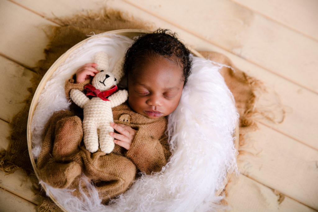 Newborn baby of colour in a bowl wearing a brown all in one onsie on a beige and white background with wooden floor baby posed curled in a bowl cute baby boy professional newborn photo session in a Studio in Wimbledon South West London SW19