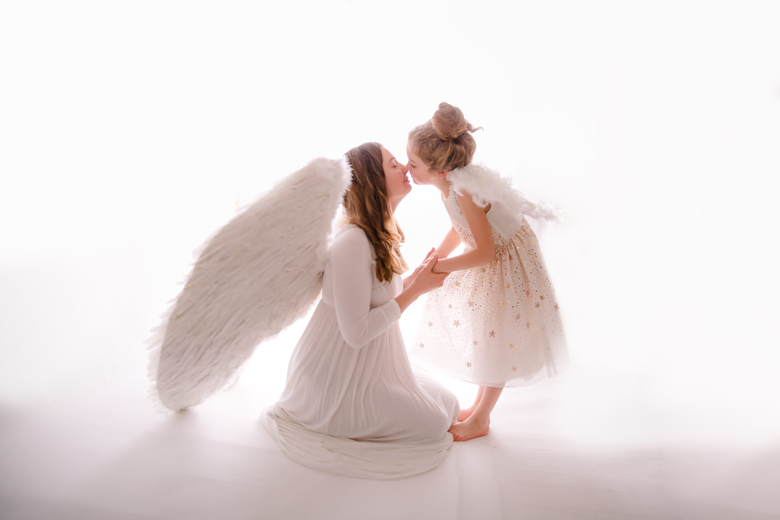 Child photography mother and daughter photography mum and daughter in white dresses tender kiss on a white background white on white angelic child portrait photographer studio family photographer in South West London Wimbledon SW19
