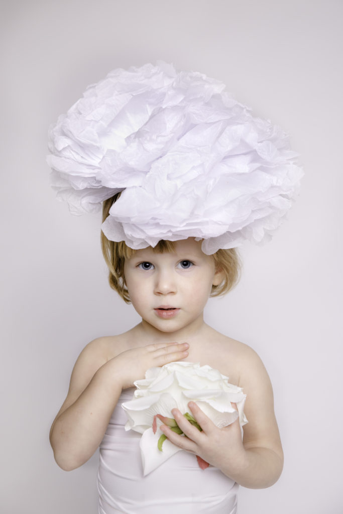 Child photography children photography kids photography child portrait girl wearing a white dress with a white flower on a white background white on white child portrait photographer studio family photographer in South West London Wimbledon SW19