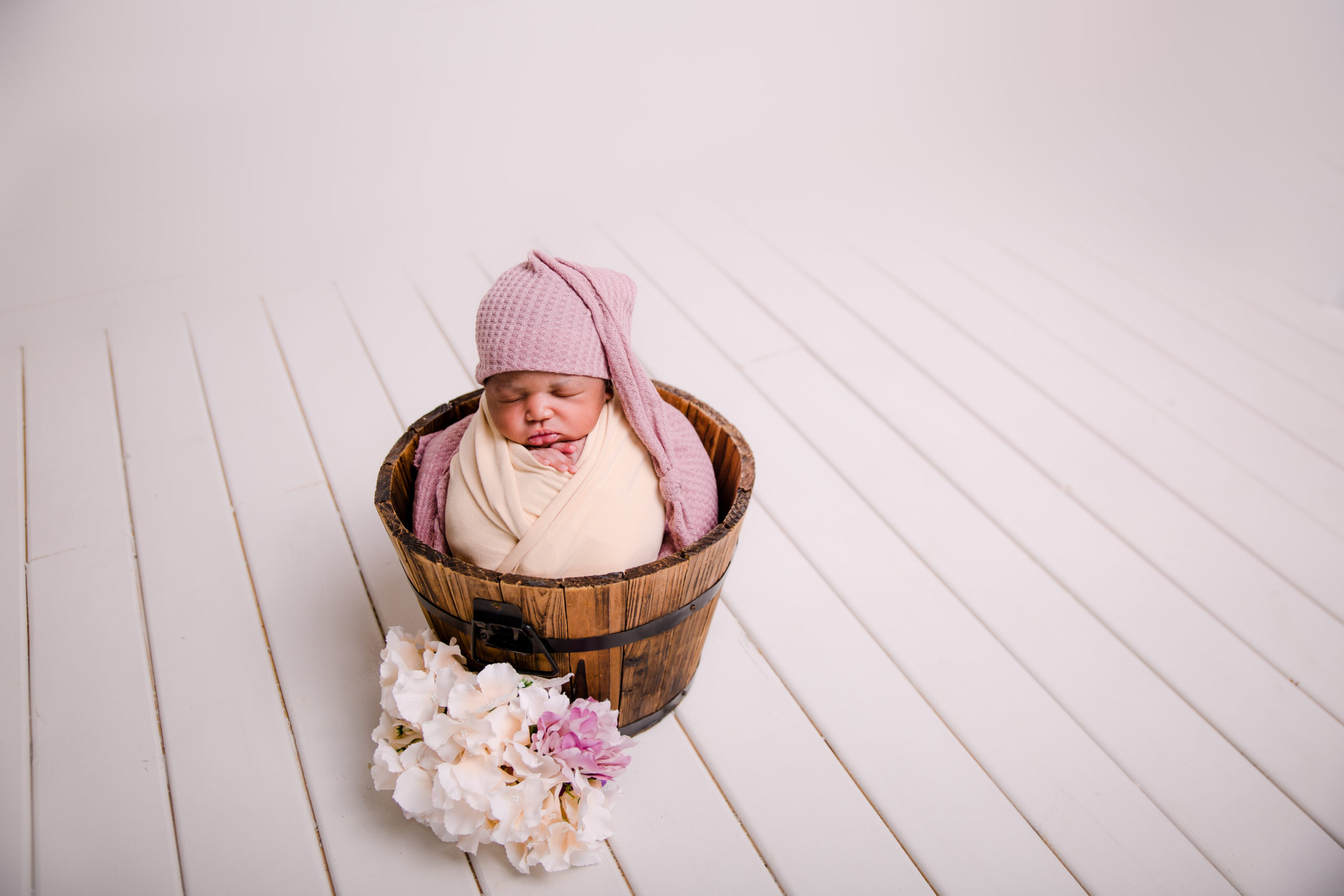 Black baby girl during her first newborn photo session in Wimbledon Studio, Baby wrapped in a beige wrap with pink hat in a bucket pose baby photo shoot in south west London SW19