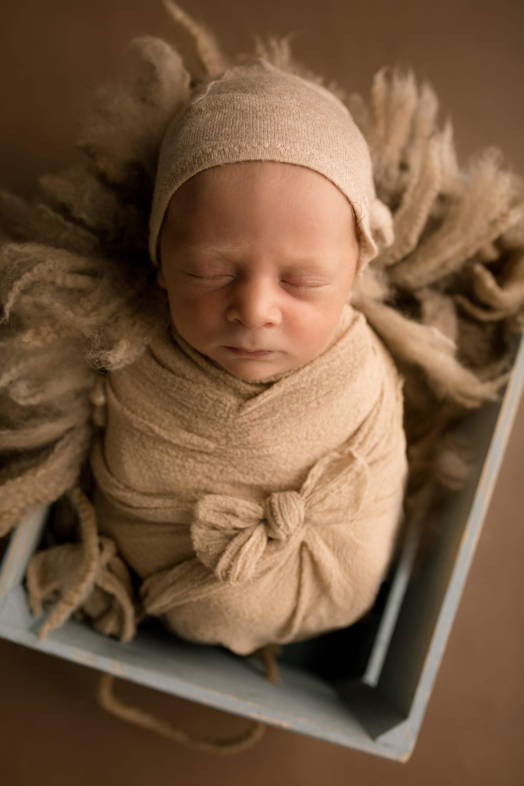 Newborn Photography tips baby boy wrapped in a beige wrap with a small bow in a blue crate. Studio newborn photography South West London Wimbledon newborn photo studio SW19