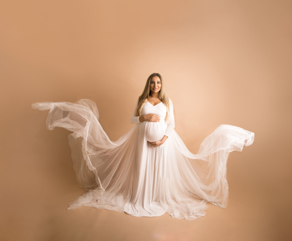 Maternity Photo Session white on white pregnancy photoshoot mother to be wearing a white dress with floating fabrics portrait image Wimbledon Photo Studio SW19