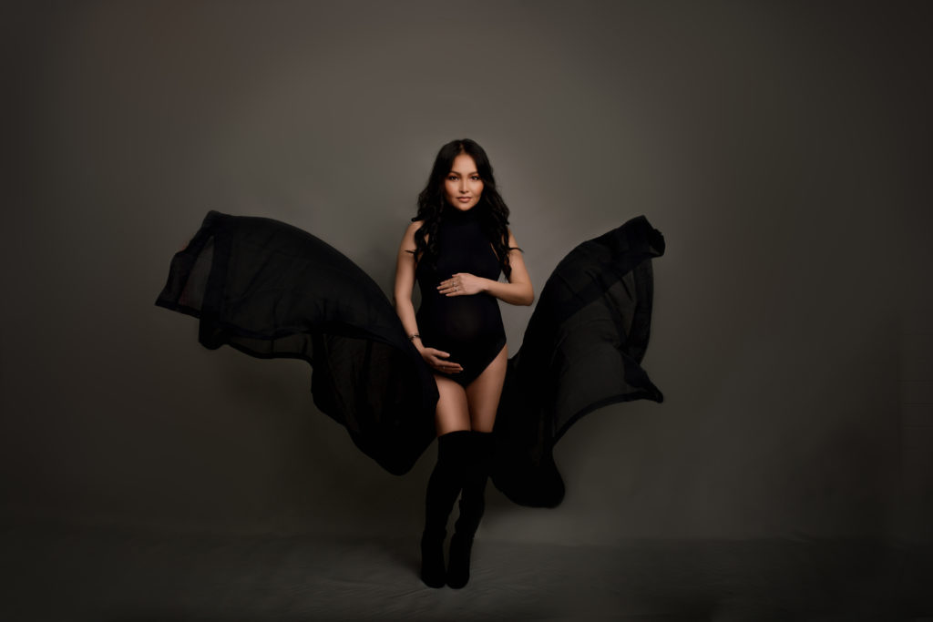 Modern black bodysuit used for a pregnancy photo session with flying fabrics in Wimbledon