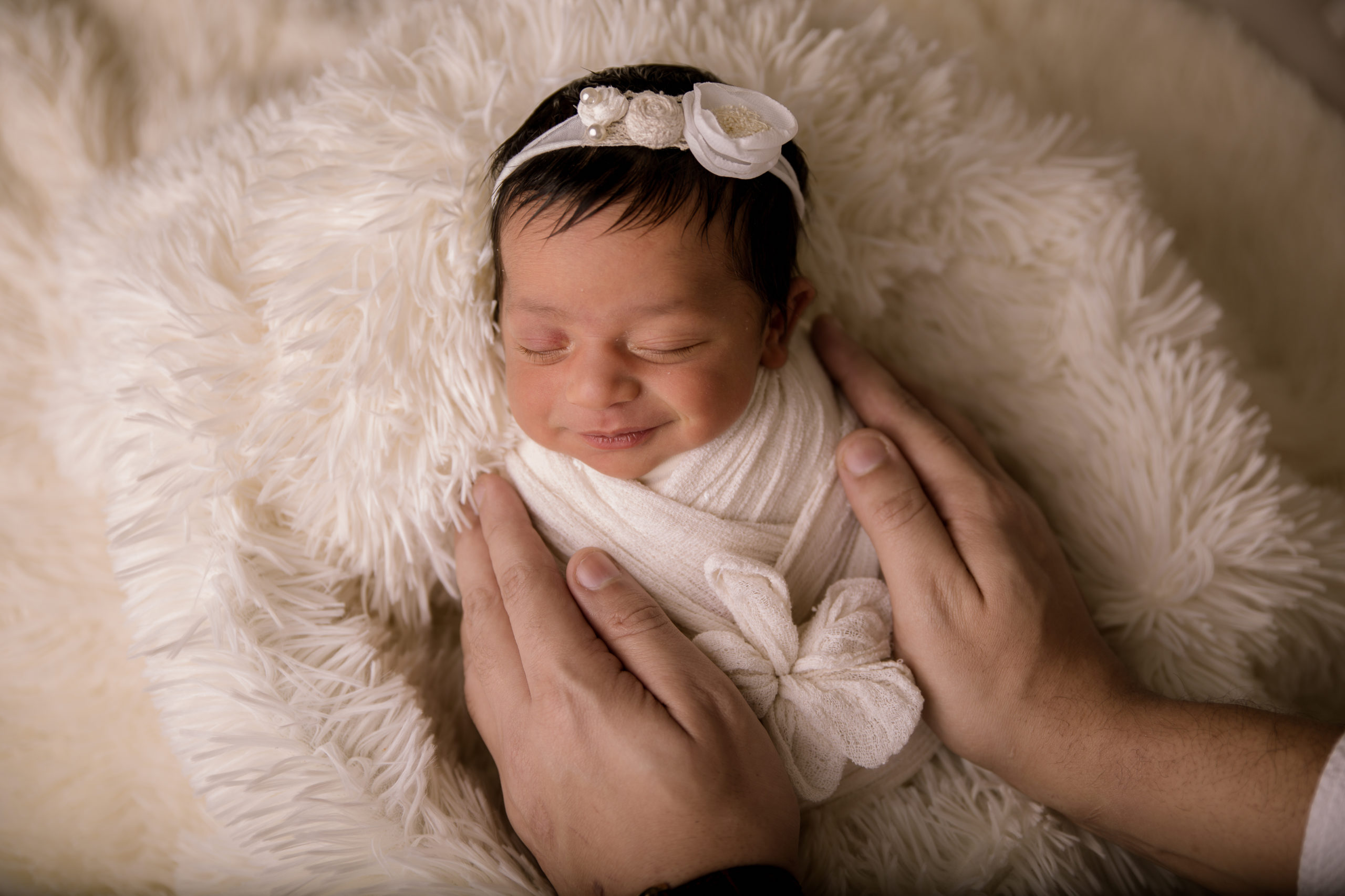 newborn photoshoot wrapped and smiling baby in daddy's hands baby photo studio in Wimbledon South west London SW19