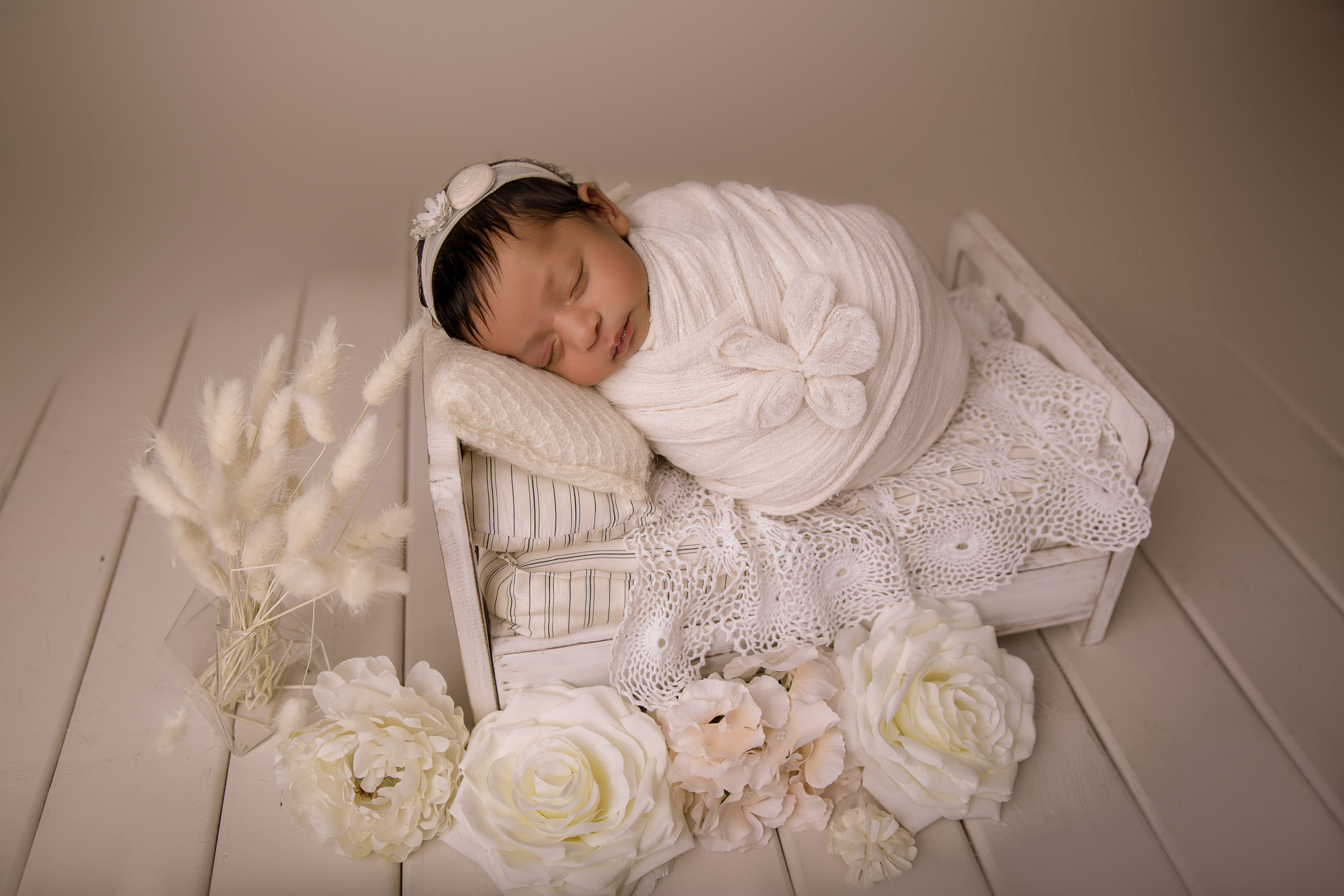 baby photoshoot wrapped in a white wrap on a white cot newborn photo studio near Kingston south West London