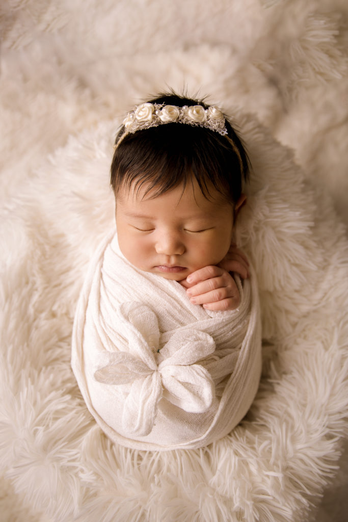 newborn photography baby photoshoot wrapped in white with a big flower Photo Studio near Kingston