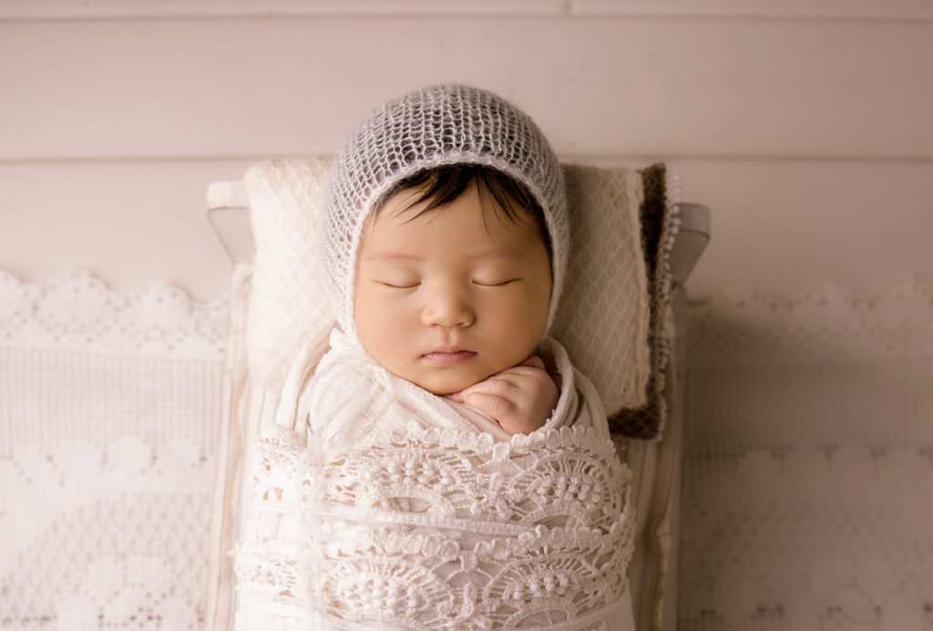 newborn photo session London baby girl in white hat on a white bed in Wimbledon Photo studio South West London