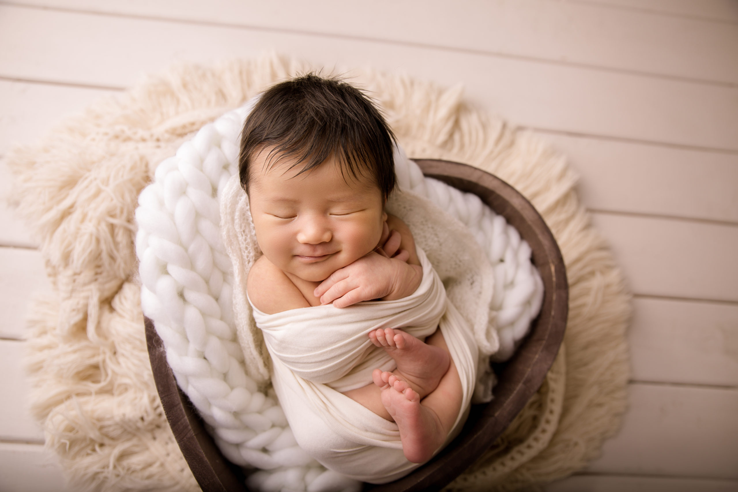 newborn photo session baby photoshoot wrapped in a heart bowl and smiling newborn photo studio near Kingston