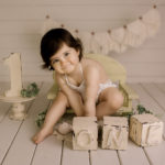 cake smash photo session smiling baby girl with letters ONE in Wimbledon photo studio South West London